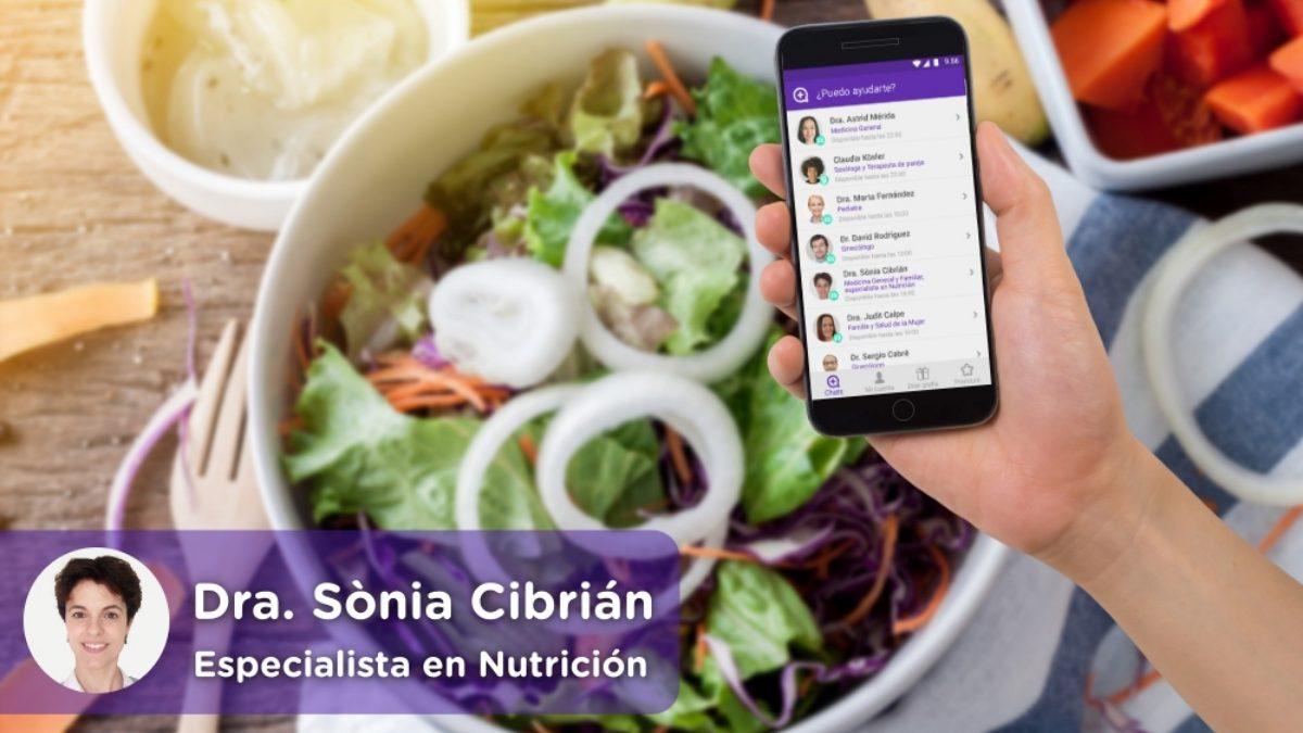 móvil con la aplicación de chat médico de mediquo. Cocina con plato lleno de alimentos saludables, ensalada, fruta, cebolla, patatas, etc. Nutricionista Dra. Sònia Cibrián