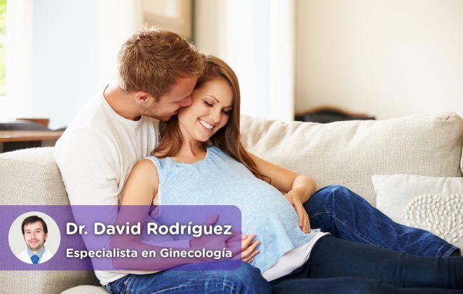 Pareja con mujer embarazada, relajados en el sofa juntos mientras esperan el nacimiento de su bebé